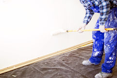 Worker house painter paints a wall Royalty Free Stock Photography