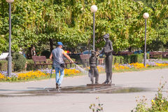 Worker of housing and communal services washes with water from the hose monument to the first teacher Volgograd Stock Image