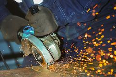 Free Worker In Gloves And Overalls Angle Grinder Cuts A Metal Sheet. Industrial Background Of The Labor Process Stock Photos - 139096823