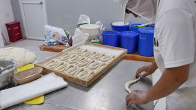 Worker in industrial bakery rolling dough pretzels stock footage