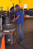 Worker inflating trye. African tyre shop worker inflating a trye with professional machine Royalty Free Stock Image