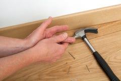 Worker injured at work. During skirting board repair stock photo