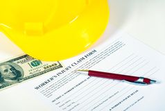 Worker injury claim hard hat with money and pen on Royalty Free Stock Image