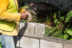 Worker inserting noise proofing sponge into barrier bricks durin Stock Image