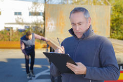 Worker inspecting empty truck Stock Photography