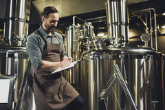 Worker inspecting equipment at brewery. Male worker in apron inspecting industrial equipment and making notes at the brewery Royalty Free Stock Photo