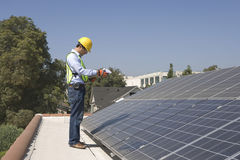 Worker Inspecting Solar Panels On Rooftop Royalty Free Stock Photography