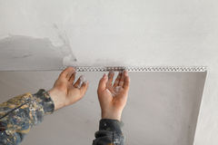 Worker install batten at ceiling and wall Royalty Free Stock Photo