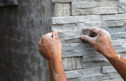 Worker install stone wall surface with cement for house Royalty Free Stock Photo