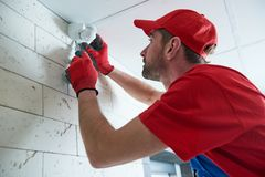 Worker installing or adjusting motion sensor detector on the ceiling. Motion sensor or movement detector installation or adjustment by construction worker on the stock photos