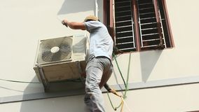 Worker is installing air conditioners in the house stock video