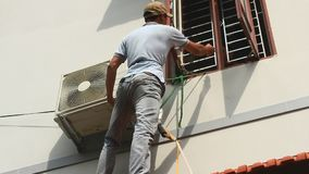 Worker is installing air conditioners in the house stock video footage
