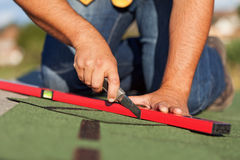 Worker installing bitumen roof shingles Stock Photo