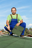 Worker installing bitumen roof shingles Stock Images