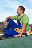 Worker installing bitumen shingles - taking a break Royalty Free Stock Image
