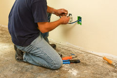 Worker installing cable inside wall Royalty Free Stock Photo