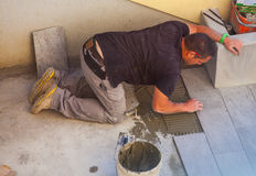 Worker Installing ceramic floor tiles Royalty Free Stock Photo