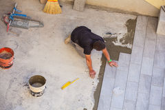 Worker Installing ceramic floor tiles Royalty Free Stock Image