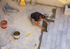 Worker Installing ceramic floor tiles Stock Photos