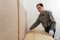 Worker installing a countertop. Construction worker installing a wooden countertop in a domestic kitchen royalty free stock photography