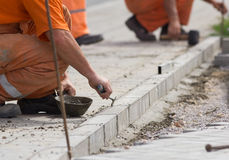 Worker installing curb stones Royalty Free Stock Image