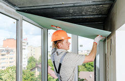 Worker is installing the drywall. royalty free stock photo