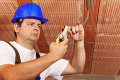 Worker installing electrical wiring. In a new building - working on the ceiling wires Royalty Free Stock Photography