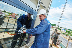 Worker installing facade window Royalty Free Stock Photo