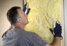 Worker installing fiberglass insulation on the wal Stock Photos