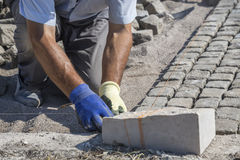 Worker installing granite cubes 2 Royalty Free Stock Photo