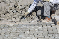 Worker installing granite cubes Stock Photography