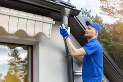 Worker installing house roof gutter system stock photos