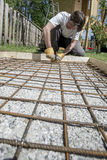 Worker installing iron rods for concrete sidewalk Stock Photos