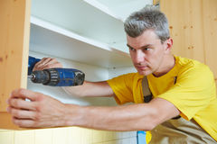 Worker installing kitchen cupboard Stock Image
