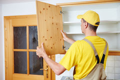 Worker installing kitchen cupboard Royalty Free Stock Photo