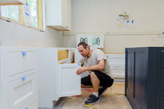 worker installing kitchen cupboard Royalty Free Stock Photography