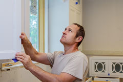 worker installing kitchen cupboard Stock Images