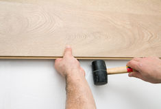 Worker installing laminate floor using a hammer Royalty Free Stock Image