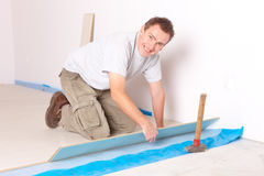 Worker installing a laminated flooring. Happy manual worker installing a laminated flooring stock photography