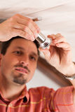 Worker is installing a luster Royalty Free Stock Image