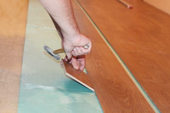 Worker installing new laminate flooring Royalty Free Stock Photo