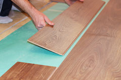 Worker installing new laminate flooring Royalty Free Stock Image