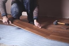 Worker installing new laminate wooden floor royalty free stock images