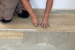 Work on laying flooring. Worker installing new vinyl tile floor. Worker installing new vinyl tile floor royalty free stock photography