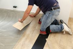 Work on laying flooring. Worker installing new vinyl tile floor. Worker installing new vinyl tile floor stock images