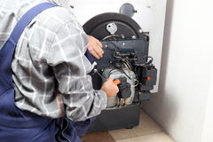 Worker is installing a oil burner. In a heating room stock photo