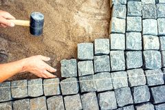 Worker installing pavement rocks, cobblestone blocks on road pavement Royalty Free Stock Image