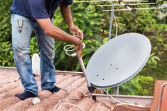 Worker installing satellite dish and antenna on roof top Stock Image