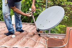 Worker installing satellite dish and antenna on roof top Stock Photo
