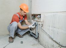 Worker is installing sewer pipes. Stock Images